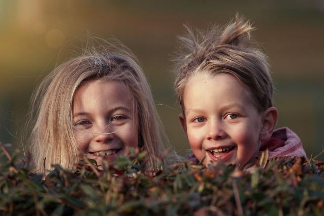 A boy and a girl peeping and smiling from behind a hedge.